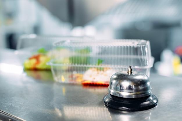 Consegna del cibo. tavolo di distribuzione in un ristorante con una campana di metallo. cibo in contenitori di plastica. panna cotta e insalata di verdure in contenitori di plastica usa e getta.