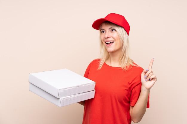 Consegna della pizza donna russa che tiene una pizza sopra il muro isolato con l'intenzione di realizzare la soluzione sollevando un dito