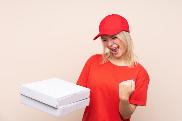 Consegna della pizza donna russa che tiene una pizza sopra la parete isolata che celebra una vittoria