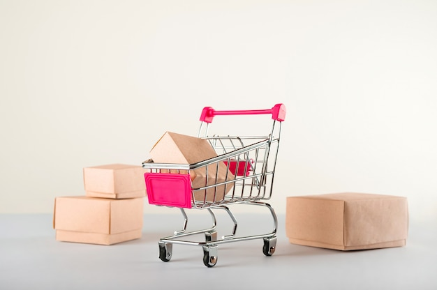 Consegna delle merci, cibo online. molte scatole su un primo piano bianco del fondo. carrello in miniatura e copia spazio.