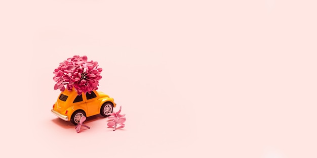 Consegna di fiori freschi per le vacanze. automobile gialla del giocattolo con il ramo del fiore lilla.