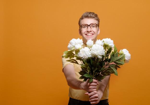 Consegna di fiori, uomo con fiori su uno sfondo giallo