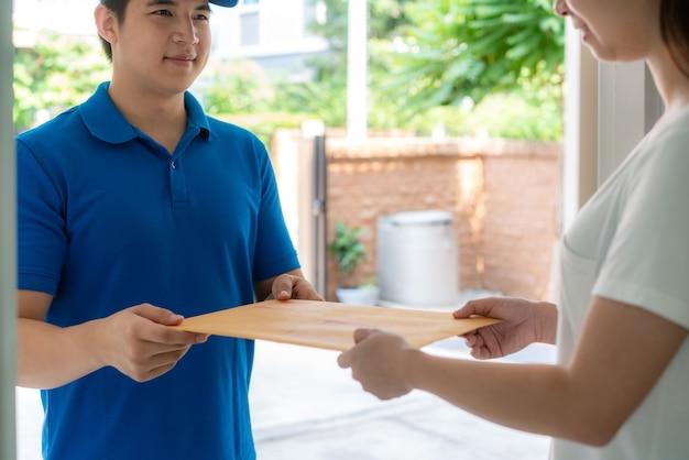 Consegna giovane uomo in uniforme blu sorriso e tenendo la lettera o la busta del documento di fronte a casa