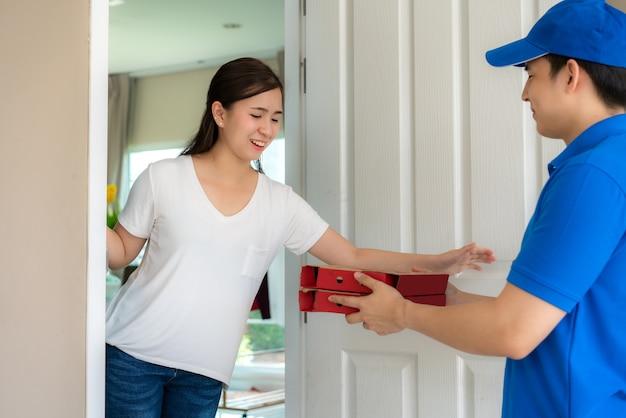 Consegna giovane uomo in uniforme blu sorriso e tenendo le scatole per la pizza in casa davanti