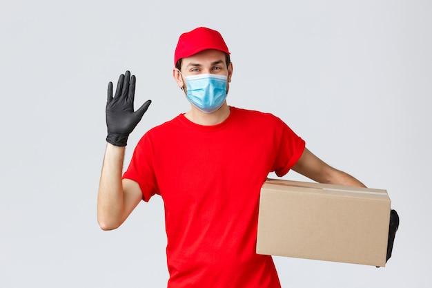 Consegna pacchi e pacchi, consegna quarantena covid-19, ordini di trasferimento. amichevole corriere in divisa rossa, maschera con guanti protettivi, consegna scatola ordine al cliente, agitando la mano in segno di saluto