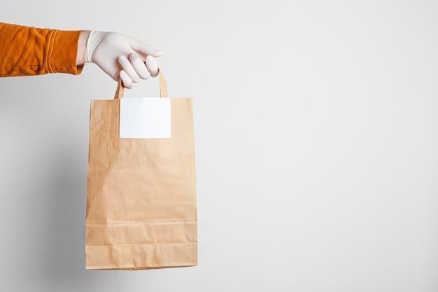 Consegna sicura dell'alimento in un sacchetto del mestiere e fattorino della pizza a casa su un fondo bianco