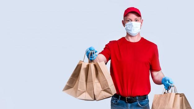 Consegna sicura. il corriere in uniforme rossa e maschera protettiva e guanti tiene un grosso ordine, molti sacchetti di carta, cibo per consegne senza contatto in quarantena.