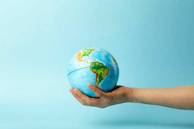 Conservazione e protezione della natura e della terra. globo terrestre in mani femminili su uno sfondo blu.