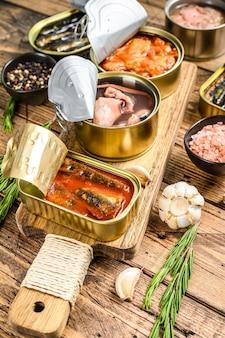 Conserve di lattine aperte con saury, salmone, spratto, sarde, calamari e tonno. fondo in legno.