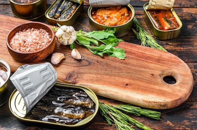 Conserve di lattine aperte con saury, salmone, spratto, sarde, calamari e tonno. sfondo in legno scuro.