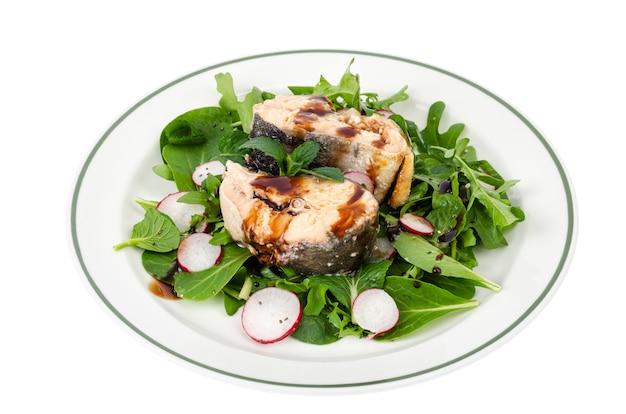 Conserve di pesce con verdure sul piatto isolato su bianco. foto di studio