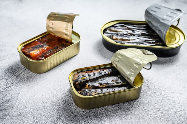 Conserve di pesce in scatola di latta sardine, sardine affumicate, sgombri. fondo di legno grigio. vista dall'alto.