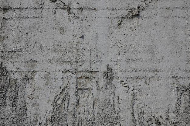 Consistenza del vecchio muro di cemento goffrato in colore grigio. immagine di sfondo di un prodotto concreto