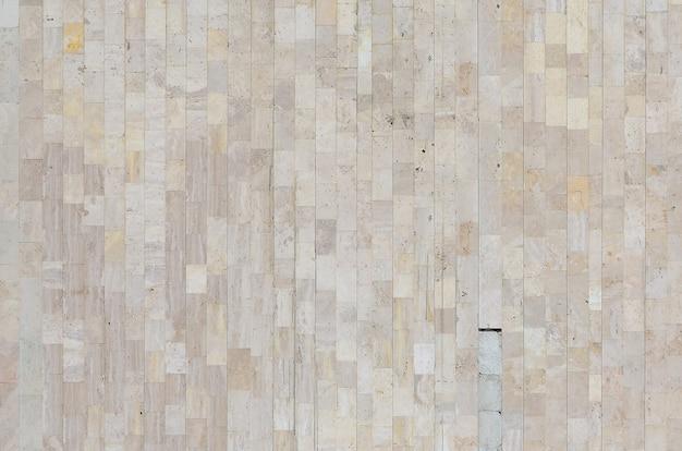 Consistenza del vecchio muro di marmo beige fatto da una varietà di piastrelle di grandi dimensioni