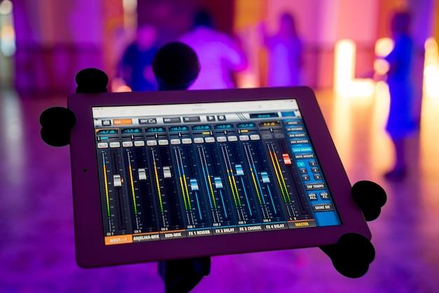 Console mixer audio e luce su tablet con microfono sopra lo sfocato. registrazione di un pannello di missaggio con un mixer digitale in studio musicale.