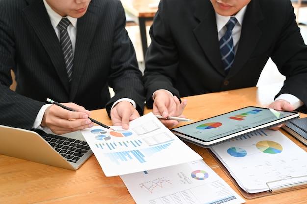 Consulente aziendale, uomo d'affari che lavora con documento finanziario e tablet con riunioni e pianificazione.