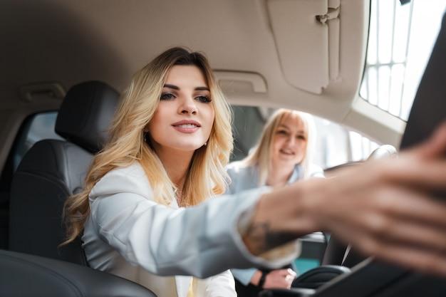 Consulente che mostra l'interno dell'auto a un cliente