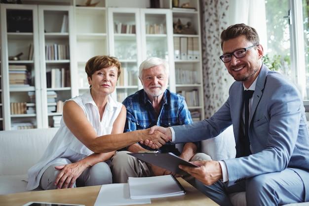 Consulente finanziario che stringe le mani con la donna senior
