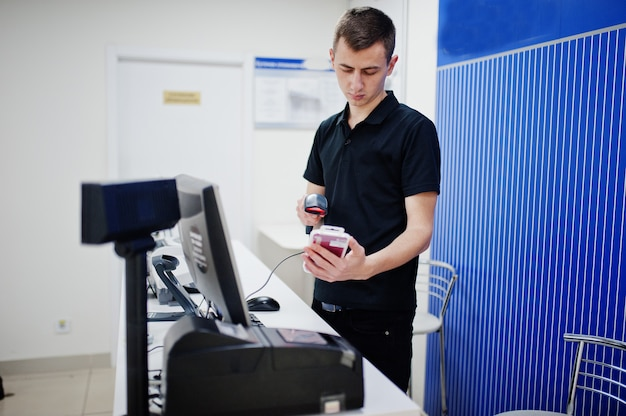 Consulente professionale di telefonia mobile venditore uomo nel negozio di tecnologia o negozio lavora alla cassa.