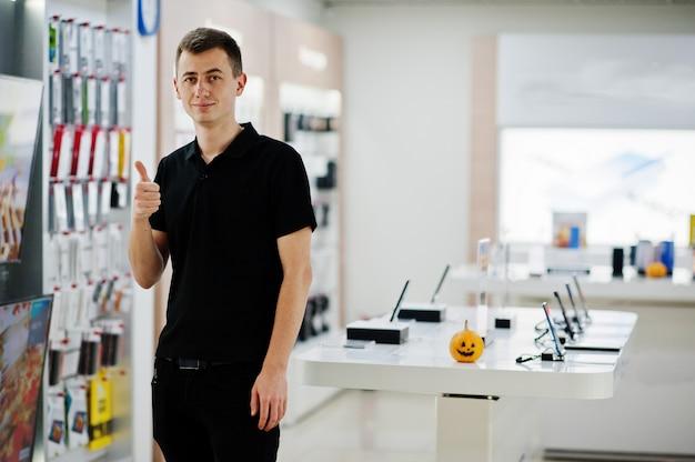 Consulente professionista del telefono mobile dell'uomo del venditore nel negozio o nel negozio di tecnologia.