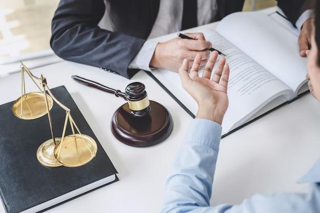 Consultazione e conferenza degli avvocati maschii e della donna di affari professionale che lavorano e che discutono avendo allo studio legale in ufficio. concetti di legge, giudice martelletto con bilancia della giustizia