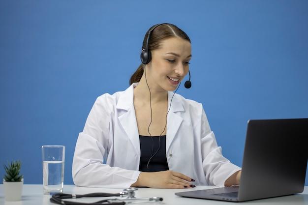 Consultazione medica online. medico attraente in headsettalking con il paziente