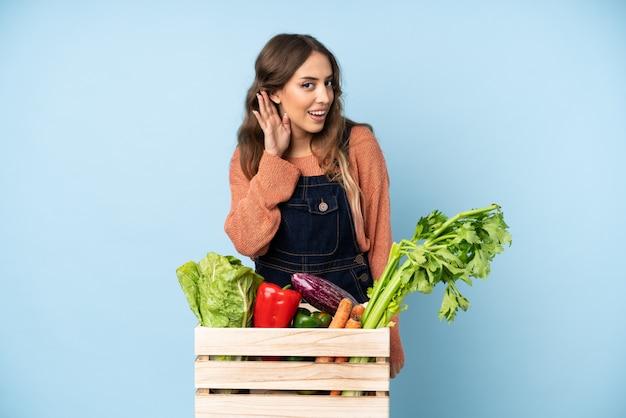 Contadino con verdure appena raccolte in una scatola ascoltando qualcosa mettendo la mano sull'orecchio