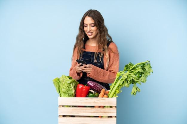 Contadino con verdure appena raccolte in una scatola che invia un messaggio con il cellulare