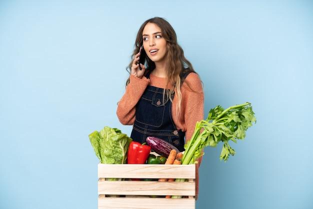 Contadino con verdure appena raccolte in una scatola che mantiene una conversazione con il telefono cellulare