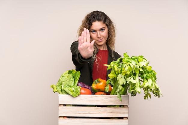 Contadino con verdure appena raccolte in una scatola isolata su beige facendo gesto di arresto con la sua mano