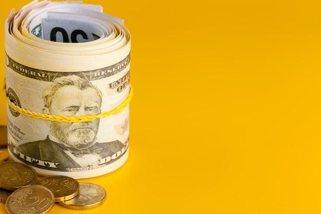 Contanti dei soldi del dollaro americano su fondo giallo.