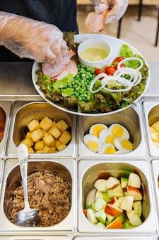 Contatore del bar dell'insalata fresca con le mani della persona che producono l'insalata di pollo in un piatto.
