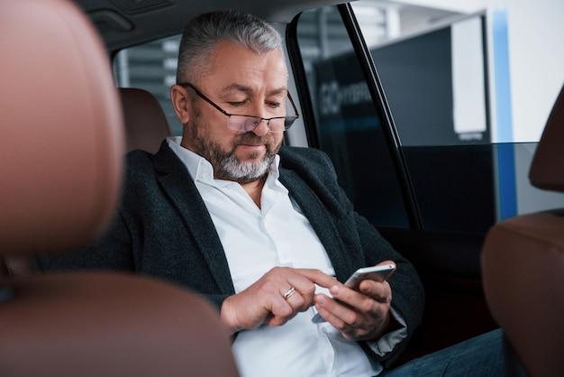 Contattare con i colleghi. utilizzando il telefono cellulare. l'uomo d'affari negli occhiali si trova nella parte posteriore della macchina moderna e ha delle offerte