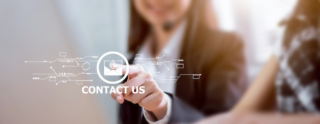 Contattateci concetto, mano della donna di affari che indica email dell'icona e call center di servizio di assistenza al cliente.