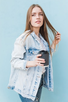 Contemplando la giovane donna che tiene il caffè a gettare che sta davanti alla parete blu