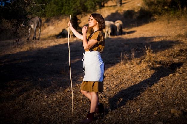 Contemplato agricoltore femminile in piedi nel campo