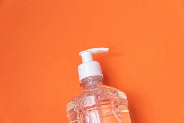Contenitore con gel alcolico sulla parete arancione