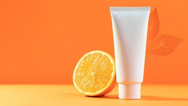 Contenitore cosmetico bianco con arancia