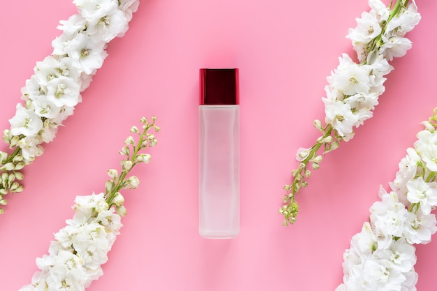 Contenitore cosmetico di lusso mock up con fiore di primavera bianco a base di erbe