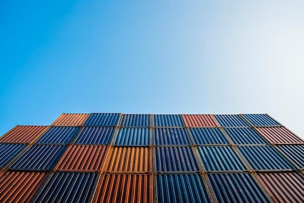 Contenitore di contenitore variopinto nel cantiere navale di logistica delle esportazioni di importazioni con cielo blu
