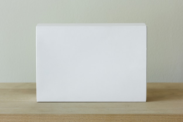 Contenitore di pacchetto di cartone bianco vuoto sul tavolo di legno