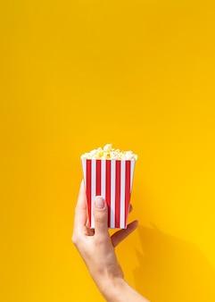 Contenitore di popcorn davanti a fondo arancio