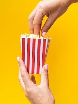 Contenitore di popcorn della tenuta della donna su fondo giallo