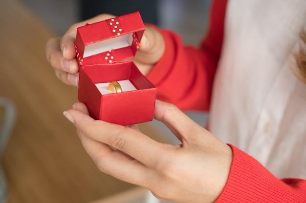Contenitore di regalo aperto della donna con l'anello di fidanzamento all'interno