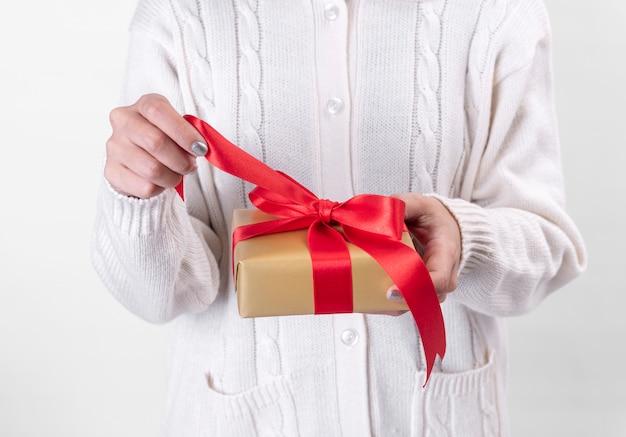 Contenitore di regalo aperto della mano delle donne su fondo bianco.