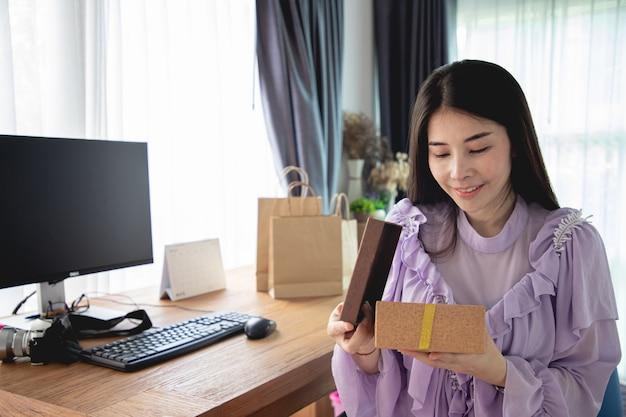 Contenitore di regalo aperto sorridente di giovane donna asiatica di natale a casa