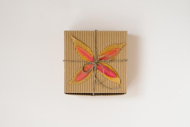 Contenitore di regalo artigianale, legato con lo spago con fiocco e foglie cadute in autunno su uno sfondo beige.