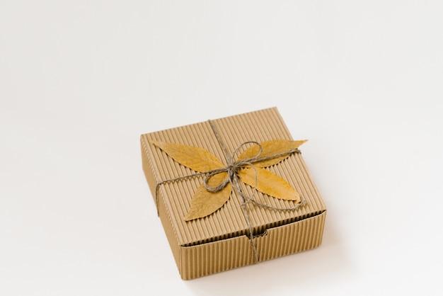 Contenitore di regalo artigianale, legato con spago con fiocco e foglie cadute in autunno su uno sfondo beige