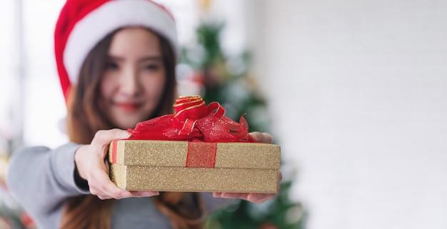 Contenitore di regalo asiatico giovane della tenuta della donna, con il fronte sorridente