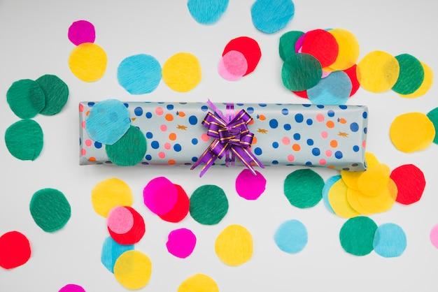 Contenitore di regalo avvolto a pois con carta colorata ritagliata circolare su fondo bianco